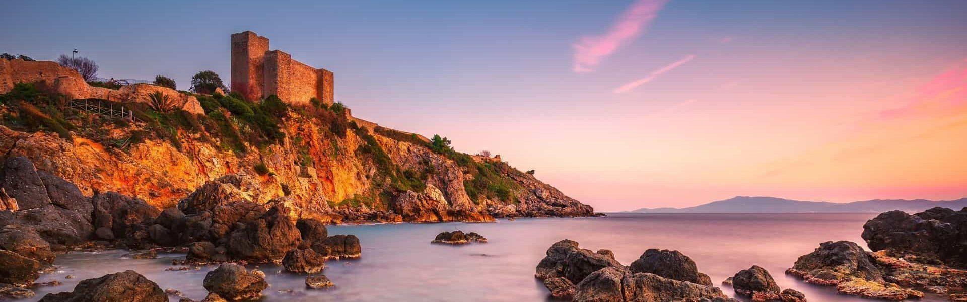 Talamone rock beach medieval fortress  sunset. Maremma Argentario, Tuscany, Italy